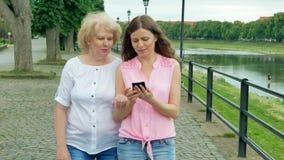 Η ευτυχής ηλικιωμένη γυναίκα και η νέα γυναίκα περπατούν κατά μήκος της προκυμαίας και χρησιμοποίηση του smartphone Ενήλικες μητέ απόθεμα βίντεο