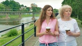 Η ευτυχής ηλικιωμένη γυναίκα και η νέα γυναίκα περπατούν κατά μήκος της προκυμαίας και του καφέ κατανάλωσης απόθεμα βίντεο