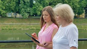 Η ευτυχής ηλικιωμένη γυναίκα και η νέα γυναίκα περπατούν κατά μήκος του υπολογιστή προκυμαιών και ταμπλετών Ποταμός στο υπόβαθρο απόθεμα βίντεο