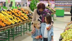 Η ευτυχής ηλικιωμένη γυναίκα με τα εγγόνια στην υπεραγορά αγοράζει τα φρούτα Πορτρέτο φιλμ μικρού μήκους