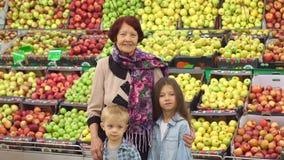 Η ευτυχής ηλικιωμένη γυναίκα με τα εγγόνια στην υπεραγορά αγοράζει τα φρούτα Πορτρέτο απόθεμα βίντεο