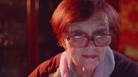 Η ευτυχής ηλικιωμένη γυναίκα στα γυαλιά εξετάζει το όργανο ελέγχου του lap-top απόθεμα βίντεο