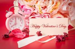 Η ευτυχής κάρτα βαλεντίνων και το ροζ ξυπνητήρι με το ροζ ανθοδεσμών αυξήθηκαν Στοκ Φωτογραφίες