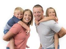 Η ευτυχής και όμορφη αμερικανική οικογένεια με το σύζυγο και τη σύζυγο που συνεχίζουν την πλάτη τους λίγος γιος και καλή νέα κόρη Στοκ Εικόνα