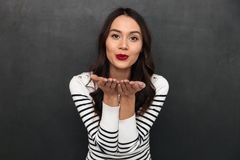 Η ευτυχής καλή γυναίκα brunette στο πουλόβερ στέλνει το φιλί αέρα Στοκ φωτογραφία με δικαίωμα ελεύθερης χρήσης