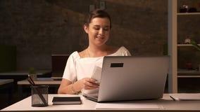 Η ευτυχής καυκάσια γυναίκα γράφει κάτω στα έγγραφα εργασίας καθμένος στο γραφείο τούβλου κοντά στο lap-top της, που χαλαρώνουν απόθεμα βίντεο