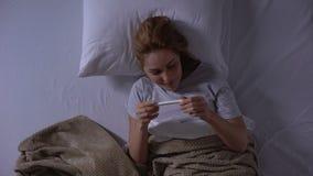 Η ευτυχής κυρία που βρίσκεται στο κρεβάτι, κράτημα εξετάζει και απόλαυση των ειδήσεων ευχαρίστησης για την εγκυμοσύνη απόθεμα βίντεο
