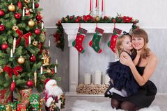 Η ευτυχής κόρη αγκαλιάζει τη μητέρα που εγκαθιστά κοντά σε μια άσπρη εστία δίπλα σε ένα χριστουγεννιάτικο δέντρο Στοκ Φωτογραφία