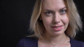 Η ευτυχής μέσης ηλικίας ξανθή επιχειρηματίας στην μπλε μπλούζα γυρίζει στη κάμερα και τα ρολόγια χαρωπά σε το στο μαύρο υπόβαθρο απόθεμα βίντεο