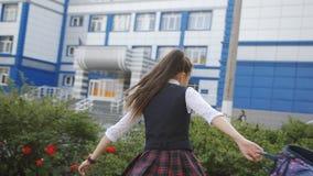 Η ευτυχής μαθήτρια χορεύει με ένα σακίδιο πλάτης διαθέσιμο και που έχει τη διασκέδαση, απολαμβάνοντας την αρχή των διακοπών απόθεμα βίντεο
