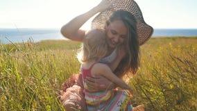 Η ευτυχής μητέρα με λίγη κόρη κάθεται στον τομέα και τον ανόητο γύρω φιλμ μικρού μήκους