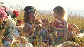 Η ευτυχής μητέρα με λίγη κόρη κάθεται στον τομέα και τον ανόητο γύρω απόθεμα βίντεο
