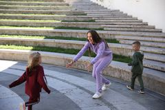 Η ευτυχής μητέρα με τα παιδιά στη μοντέρνη οικογένεια ενδυμάτων κοιτάζει σε ένα πάρκο στοκ φωτογραφίες