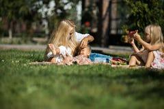 Η ευτυχής μητέρα με τα παιδιά έχει τη διασκέδαση στη χλόη Στοκ φωτογραφία με δικαίωμα ελεύθερης χρήσης
