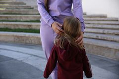 Η ευτυχής μητέρα με την κόρη στη μοντέρνη οικογένεια ενδυμάτων κοιτάζει σε ένα πάρκο στοκ εικόνα με δικαίωμα ελεύθερης χρήσης