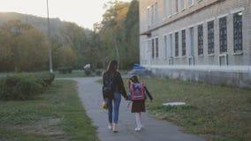Η ευτυχής μητέρα με την κόρη της στη σχολική στολή πηγαίνει στο σπίτι Το Mom και η κόρη περπατούν κατά μήκος της αλέας κατά μήκος απόθεμα βίντεο