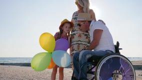 Η ευτυχής μητέρα με τη μεγάλη κοιλιά επικοινωνεί με την κόρη και το σύζυγο στην αναπηρική καρέκλα, εγκυμοσύνη, με ειδικές ανάγκες φιλμ μικρού μήκους