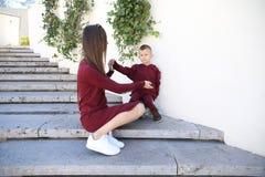 Η ευτυχής μητέρα με το γιο στη μοντέρνη οικογένεια ενδυμάτων κοιτάζει σε ένα πάρκο στοκ εικόνες με δικαίωμα ελεύθερης χρήσης