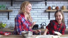 Η ευτυχής μητέρα με το παιχνίδι κορών στην κουζίνα, μικρό κορίτσι έβαλε το αλεύρι στο πρόσωπο μαμών απόθεμα βίντεο