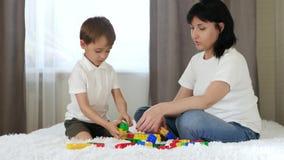 Η ευτυχής μητέρα ξοδεύει το χρόνο με το παιδί της που παίζει στους χρωματισμένους φραγμούς φιλμ μικρού μήκους