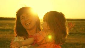 Η ευτυχής μητέρα περπατά με την κόρη της στα όπλα της στις ακτίνες του ηλιοβασιλέματος Το Mom μιλά με το ευτυχές μωρό, το μωρό εί απόθεμα βίντεο