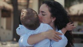Η ευτυχής μητέρα που αγκαλιάζει το παιδί της στο χαριτωμένο παιδί ακτώ απόθεμα βίντεο