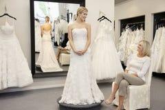 Η ευτυχής μητέρα που εξετάζει τη νέα κόρη έντυσε στη γαμήλια εσθήτα στη νυφική μπουτίκ Στοκ φωτογραφία με δικαίωμα ελεύθερης χρήσης