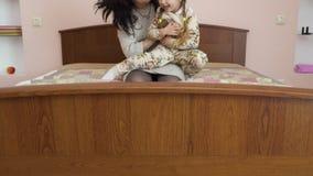 Η ευτυχής μητέρα την αγκαλιάζει λίγη κόρη στο κρεβάτι απόθεμα βίντεο