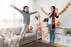 Η ευτυχής μητέρα φαίνεται το χαριτωμένο άλμα μυγών παιχνιδιού κοριτσιών της Στοκ φωτογραφίες με δικαίωμα ελεύθερης χρήσης