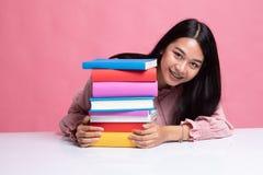 Η ευτυχής νέα ασιατική γυναίκα διάβασε ένα βιβλίο με τα βιβλία στον πίνακα στοκ εικόνες με δικαίωμα ελεύθερης χρήσης