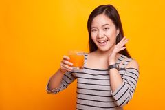 Η ευτυχής νέα ασιατική γυναίκα πίνει το χυμό από πορτοκάλι Στοκ φωτογραφία με δικαίωμα ελεύθερης χρήσης