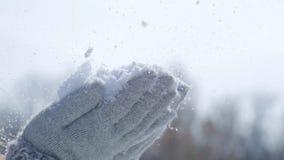 Η ευτυχής νέα γυναίκα έχει τη διασκέδαση και απολαμβάνει το φρέσκο χιόνι στην όμορφη χειμερινή ημέρα Κορίτσι στα θερμά γάντια που απόθεμα βίντεο