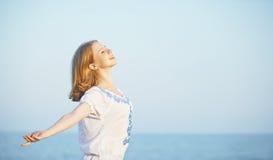 Η ευτυχής νέα γυναίκα ανοίγει τις αγκάλες της στον ουρανό και τη θάλασσα Στοκ Εικόνες
