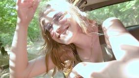 Η ευτυχής νέα γυναίκα κλίνει έξω το παράθυρο αυτοκινήτων απόθεμα βίντεο