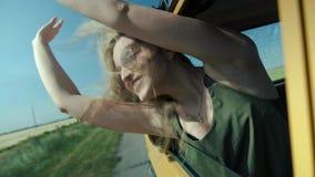 Η ευτυχής νέα γυναίκα κλίνει έξω το παράθυρο αυτοκινήτων φιλμ μικρού μήκους