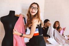 Η ευτυχής νέα γυναίκα ντύνει το σχεδιαστή στο ατελιέ στοκ εικόνες