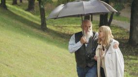 Η ευτυχής νέα γυναίκα περπατά με τον ηληκιωμένο κάτω από την ομπρέλα στο πάρκο κατά τη διάρκεια της βροχής φιλμ μικρού μήκους