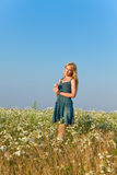 Η ευτυχής νέα γυναίκα στον τομέα των camomiles. Πορτρέτο σε μια ηλιόλουστη ημέρα Στοκ Φωτογραφίες