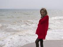 Η ευτυχής νέα γυναίκα στο κόκκινο φόρεμα έχει τη διασκέδαση στον απότομο βράχο παραλιών Στοκ Φωτογραφίες