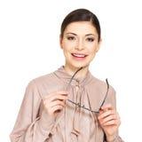 Η ευτυχής νέα γυναίκα στο μπεζ πουκάμισο κρατά τα γυαλιά Στοκ Φωτογραφίες