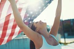 Η ευτυχής νέα εκμετάλλευση ΗΠΑ γυναικών σημαιοστολίζει τα γενικά έξοδα Στοκ εικόνα με δικαίωμα ελεύθερης χρήσης