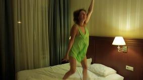 Η ευτυχής νέα ενήλικη γυναίκα στο πράσινο φόρεμα πηδά στο κρεβάτι στο διαμέρισμα Χαρά, θετικές συγκινήσεις, απόλαυση απόθεμα βίντεο