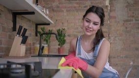 Η ευτυχής νέα θηλυκή νοικοκυρά στα λαστιχένια γάντια για τον καθαρισμό σκουπίζει τα σκονισμένα έπιπλα στην κουζίνα απόθεμα βίντεο