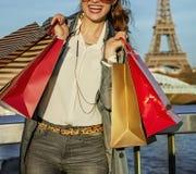 Η ευτυχής νέα καθιερώνουσα τη μόδα γυναίκα με τις αγορές τοποθετεί σε σάκκο κοντά στον πύργο του Άιφελ Στοκ Φωτογραφίες