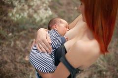 Η ευτυχής νέα μητέρα θηλάζει το νεογέννητο μωρό στον περίπατο Στοκ φωτογραφία με δικαίωμα ελεύθερης χρήσης