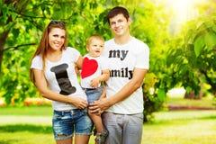 Η ευτυχής νέα οικογένεια έχει τη διασκέδαση στο πράσινο outdoo θερινών πάρκων στοκ φωτογραφία με δικαίωμα ελεύθερης χρήσης