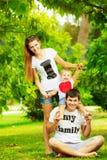 Η ευτυχής νέα οικογένεια έχει τη διασκέδαση στο πράσινο outdoo θερινών πάρκων στοκ εικόνα