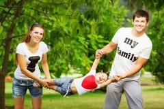 Η ευτυχής νέα οικογένεια έχει τη διασκέδαση στο πράσινο outdoo θερινών πάρκων στοκ φωτογραφία