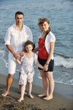 Η ευτυχής νέα οικογένεια έχει τη διασκέδαση στην παραλία Στοκ Φωτογραφία
