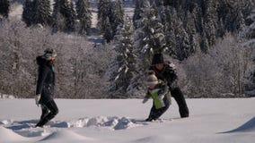 Η ευτυχής νέα οικογένεια έχει το παιχνίδι διασκέδασης στο χιόνι Ρίχνουν το χιόνι και το γέλιο Επίσης χαρούμενα περιέρχονται στο χ φιλμ μικρού μήκους